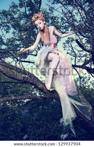 Lovely young lady wearing elegant white dress with roses standing on the tree in wood - stock photo