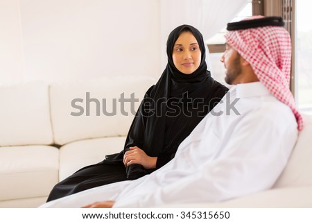 lovely young muslim couple sitting on sofa and talking at home - stock photo