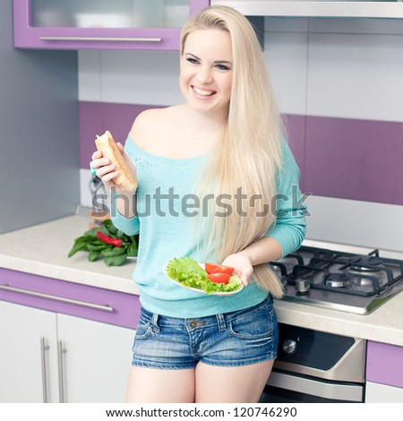Lovely young pregnant woman enjoying fresh bread and salad  in her modern kitchen. indoor shot - stock photo