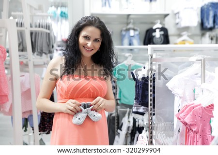 Lovely young pregnant woman looking for some baby clothes in a store for her new baby.