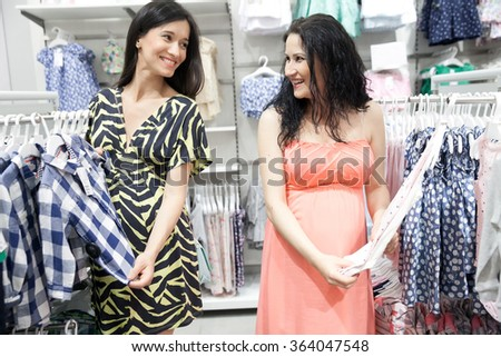 Lovely young pregnant women looking for some baby clothes in a store for their new babies.