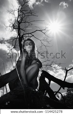 Lovely young pretty girl sitting on wood in owl mask black and white photo. Outdoor shot - stock photo