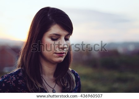 Lovely young sad girl, against green natural scenery