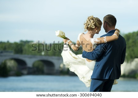 Lovely young wedding pair of man in blue suit holding blonde woman in white dress with bouquet of calla flowers on hands and spinning on water body and bridge background, horizontal picture
