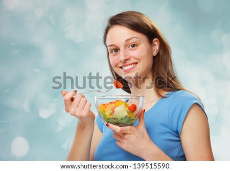 Lovely young woman enjoying a mouthful of salad