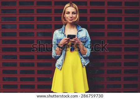 Lovely young woman holding mobile phone in hands and look to the camera smiling, attractive hipster girl with smart phone against blank copy space bright background for your content or text message - stock photo
