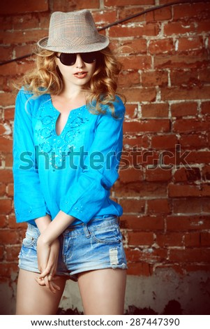 Lovely young woman in casual blouse and sunglasses outdoor. Fashion shot. - stock photo