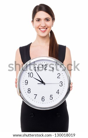 Lovely young woman in fashionable clothing displaying a wall clock.