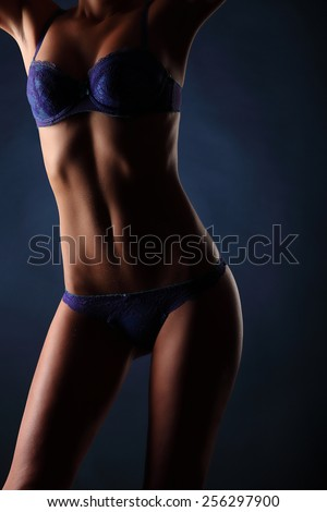 lovely young woman in lingerie body posing over dark blue background, studio