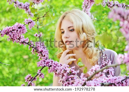 lovely young woman in spring flowers garden - stock photo