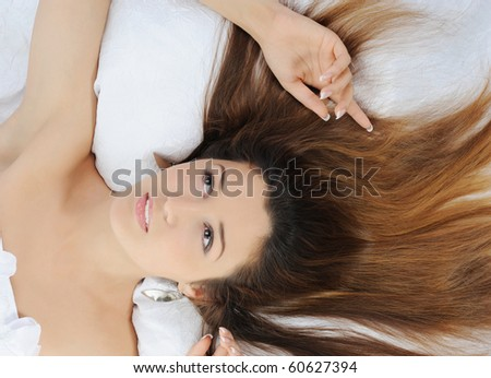 lovely young woman lying on the bed. Isolated on white background