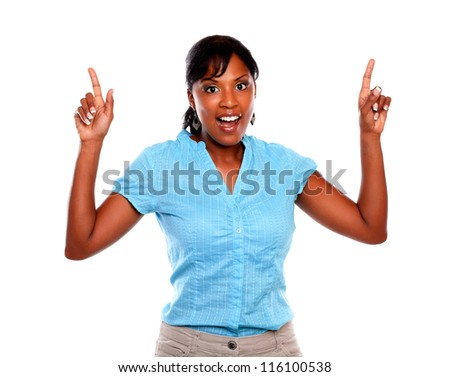 Lovely young woman pointing up and looking at you on blue shirt against white background - copyspace - stock photo
