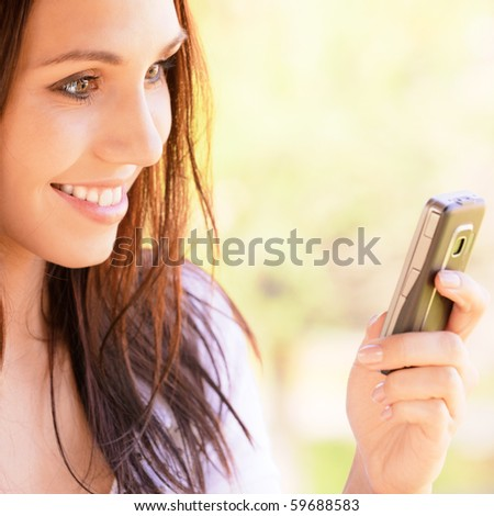 Lovely young woman reads sms on mobile phone - stock photo