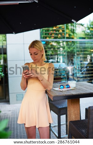 Lovely young woman sending text message with her mobile phone, charming hipster girl chatting on cell phone standing at coffee shop, female tourist connecting to wireless on telephone for browsing - stock photo