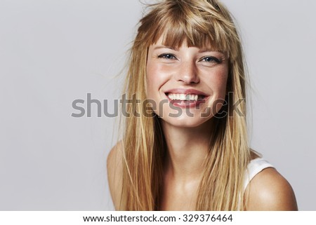 Lovely young woman smiling in studio - stock photo