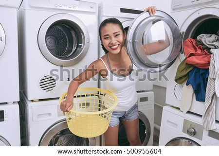 Lovely young woman taking fresh clean clothes out of washing machine