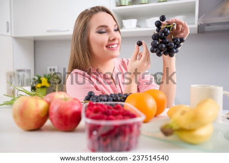 Lovely young woman with a grapes keeping to a healthy vegetable eating - stock photo