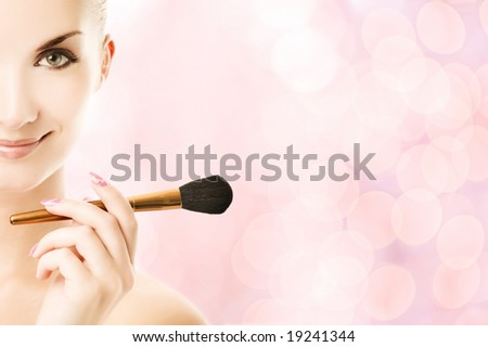 Lovely young woman with a make-up brush - stock photo