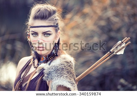 Lovely young woman with a painted face Amazon hiding in the reeds with a bow and arrows, hunting or guarding territory - stock photo