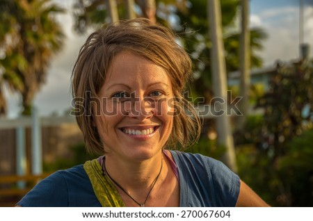 Lovely young woman with chin-length, windblown, brown hair and a beautiful smile. - stock photo