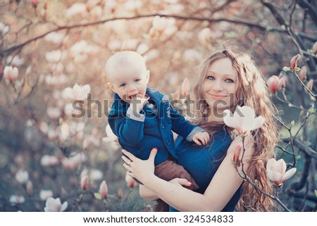 Lovely young woman with long wavy hair in a blue dress in the spring beautiful garden among the blooming magnolia with a male child in her arms, mother and son