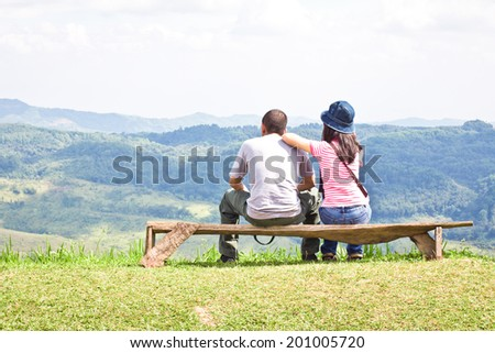 Lover sitting and viewing scenic mountain view.