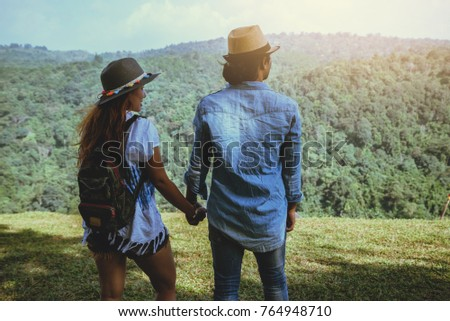 Lover women and men asians travel relax in the holiday. Standing hand in the park on the lawn. Mountain Park happily. In Thailand