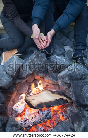 Lovers around the campfire. Hands around the campfire. Bonfire. Firewood. Fire. Fireplace. On the street. On open air. Bask. Cold. Heat. - stock photo
