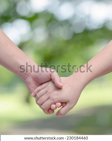 Lovers couple holding hands in the garden - stock photo