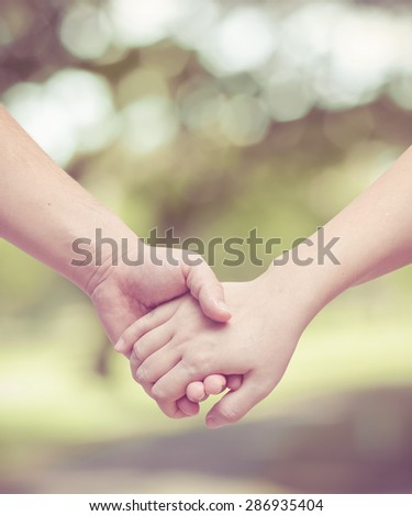 Lovers couple holding hands in the garden with vintage filter - stock photo