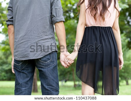 Lovers couple holding hands in the park - stock photo