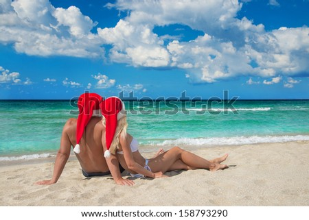 Lovers couple in red santa hats relaxing at tropical sandy beach - stock photo