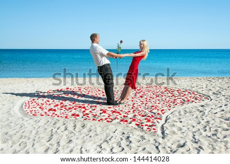 lovers couple in the heart of roses petals on sea beach in summer day - romantic proposal concept - stock photo