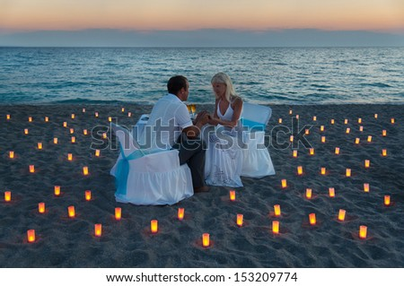 lovers couple share a romantic dinner with candles on sandy sea beach during sunset - stock photo