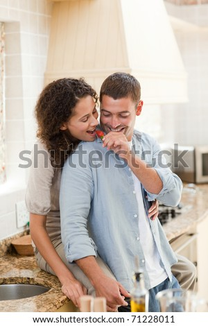 Lovers eating a strawberry in their kitchen at home
