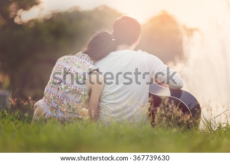 Lovers in a lake. Young couple in love sitting on the park ground near the water while these young man playing guitar in sunset time. Post processing in vintage style - stock photo