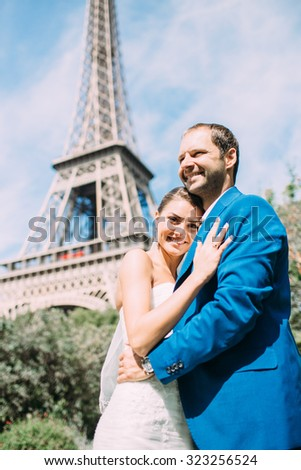 Lovers in Paris, a romantic walk through Paris in a beautiful wedding dress. Against the background of the Eiffel Tower