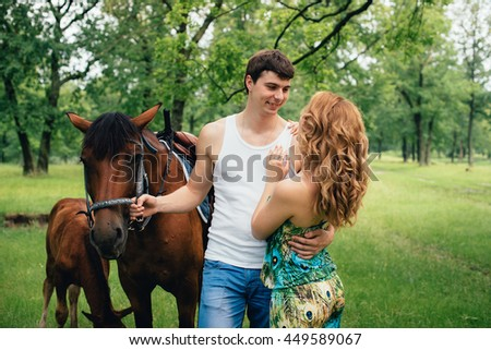 Lovers kissing and hugging on the background of horses