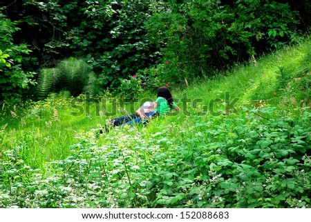 Lovers kissing and touching in the grass.