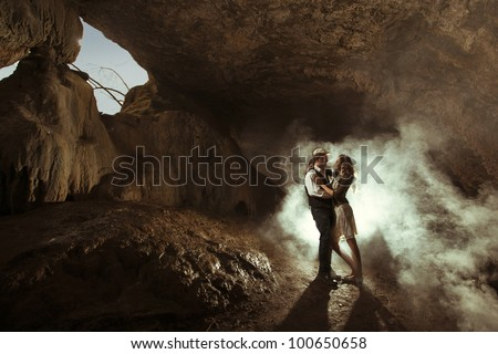 lovers kissing in a cave underground - stock photo