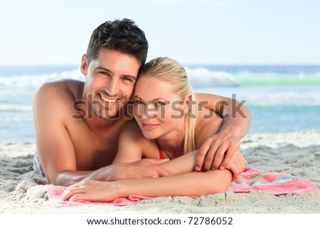 Lovers lying down on the beach - stock photo