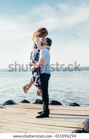 lovers on a wooden pier, river and summer nature