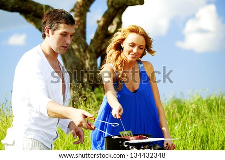 lovers on picnic cook steak - stock photo