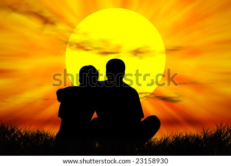 Lovers on the grass in front of the sunset