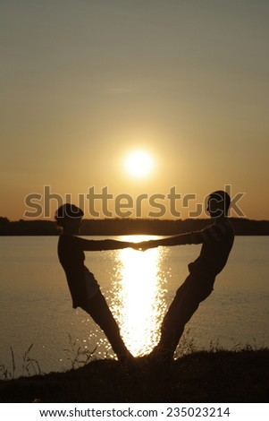 Lovers on the lake at sunset - stock photo