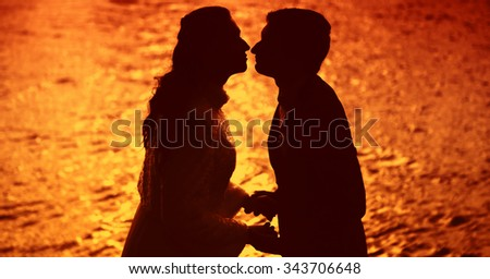 Lovers on the sunset. The kiss of lovers on a background of the sea. The red sunset. The romance of love. Backlight shot of a pair of lovers. Honeymoon at sea. - stock photo