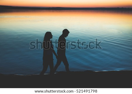 Lovers silhouette guy and girl on a background of lake