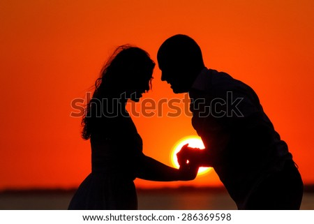 lovers silhouetted against a setting sun on the beach