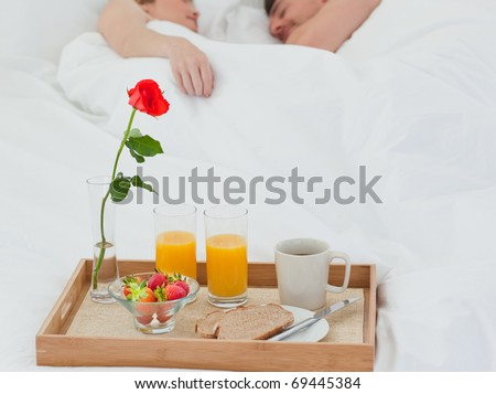 Lovers sleeping after having breakfast in their bed - stock photo