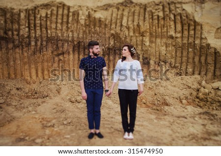Lovers standing near a clay wall